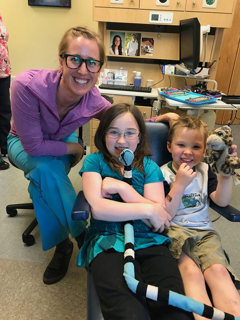 Dr. Kristin Lawson smiles with two young patients in her office